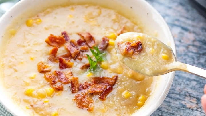 Instant Pot Loaded Potato Soup, a pressure cooker potato soup recipe, showing a white bowl filled with soup and a spoon with a spoonful of soup.