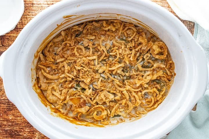 Crockpot Green Bean Casserole, a green bean casserole for a crowd, showing cooked casserole with French fried onions on the top.