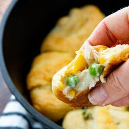 A hand is holding a chicken pot pie filled crescent roll with more crescents in a skillet blurred in the background.