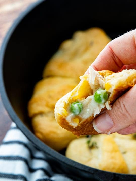 Chicken Pot Pie with Crescent Rolls, a crescent roll chicken pot pie recipe, showing a hand holding a mini pot pie.