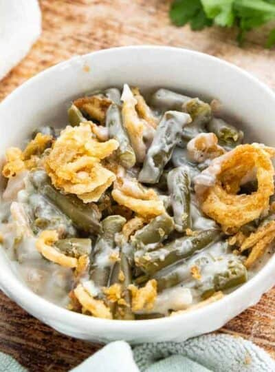 A white bowl filled with green bean casserole with French fried onions on top.