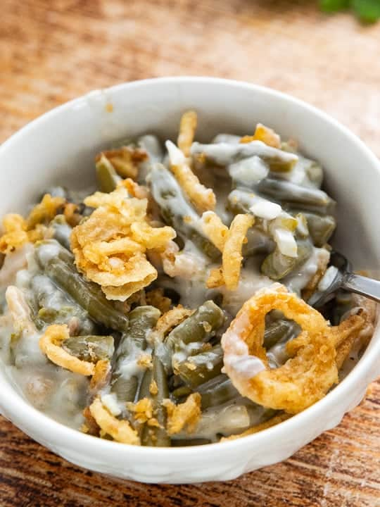 Crockpot Green Bean Casserole, a green bean casserole for a crowd, showing casserole in a white bowl on top of a wooden surface.