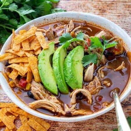 A bowl of chicken tortilla soup in a white bowl with tortilla chips and fresh avocado.