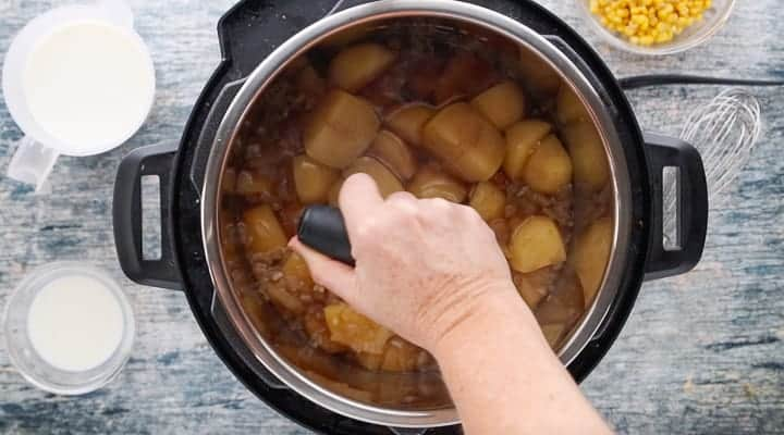 Instant Pot Loaded Potato Soup, a pressure cooker potato soup recipe, showing the potatoes in the instant pot being mashed with small glass bowls of ingredients surrounding the instant pot all on top of a wooden surface.