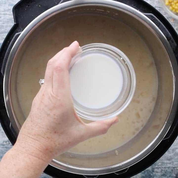 Instant Pot Loaded Potato Soup, a pressure cooker potato soup recipe, showing a cornstarch slurry in a glass bowl being held above the instant pot filled with soup.
