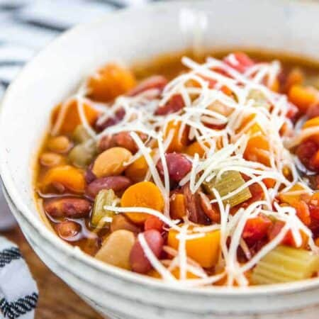 Minestrone soup in a white bowl packed with bean, carrots and celery with shredded cheese on top.
