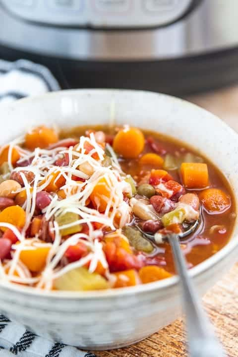 instant pot minestrone soup shown in a white bowl showing carrots, celery and beans topped with parmesan cheese with an instant pot in the background.