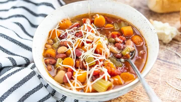 instant pot minestrone soup shown in a white bowl showing carrots, celery and beans topped with parmesan cheese.