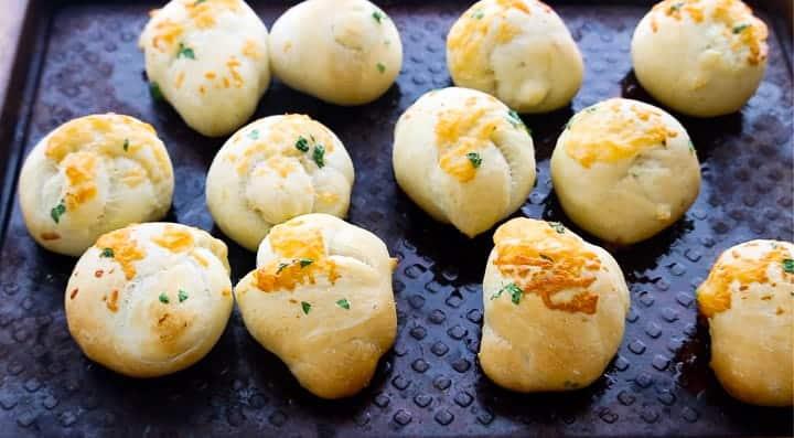 Parmesan Rhodes Rolls, a frozen dinner rolls recipe, showing Rhodes rolls on a baking sheet.