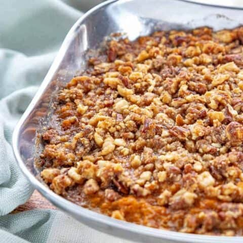 a stainless steel bowl with sweet potato crunch with a brown sugar and pecan topping.