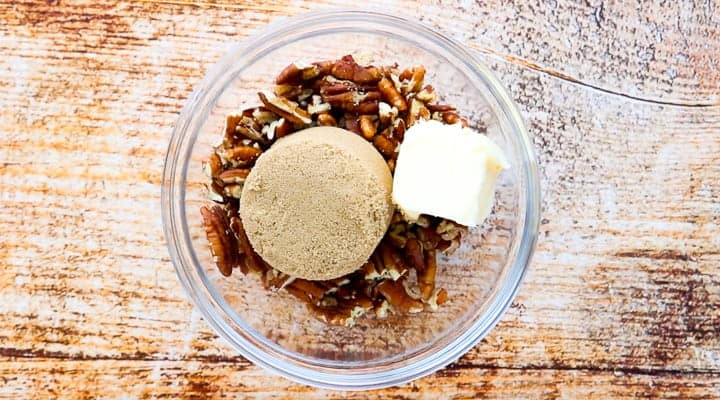 Sweet Potato Crunch, a sweet potato casserole with canned yams, showing the pecans, brown sugar and butter in a large glass bowl.