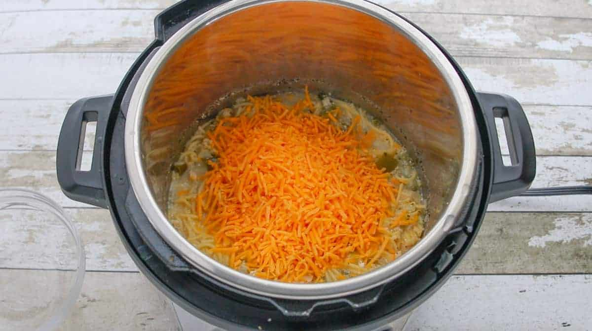 shredded cheese being added to the instant pot.