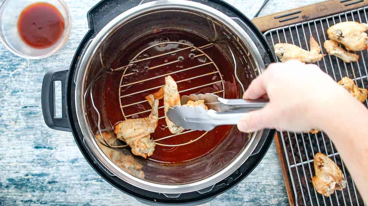 tongs scooping the cooked chicken wings from the instant pot and placing each wing on the wire rack that is on the baking sheet.