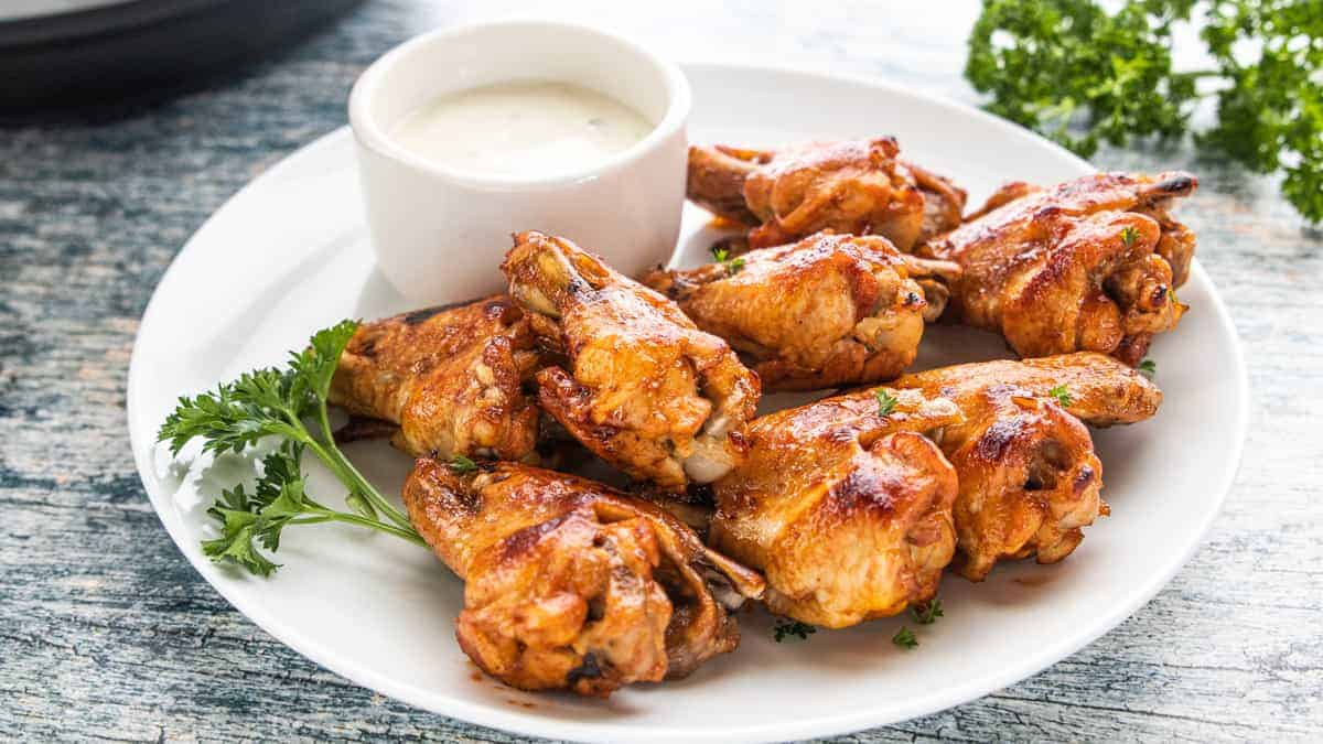 Chicken Wings being shown on a white plate with dipping sauce on the side.