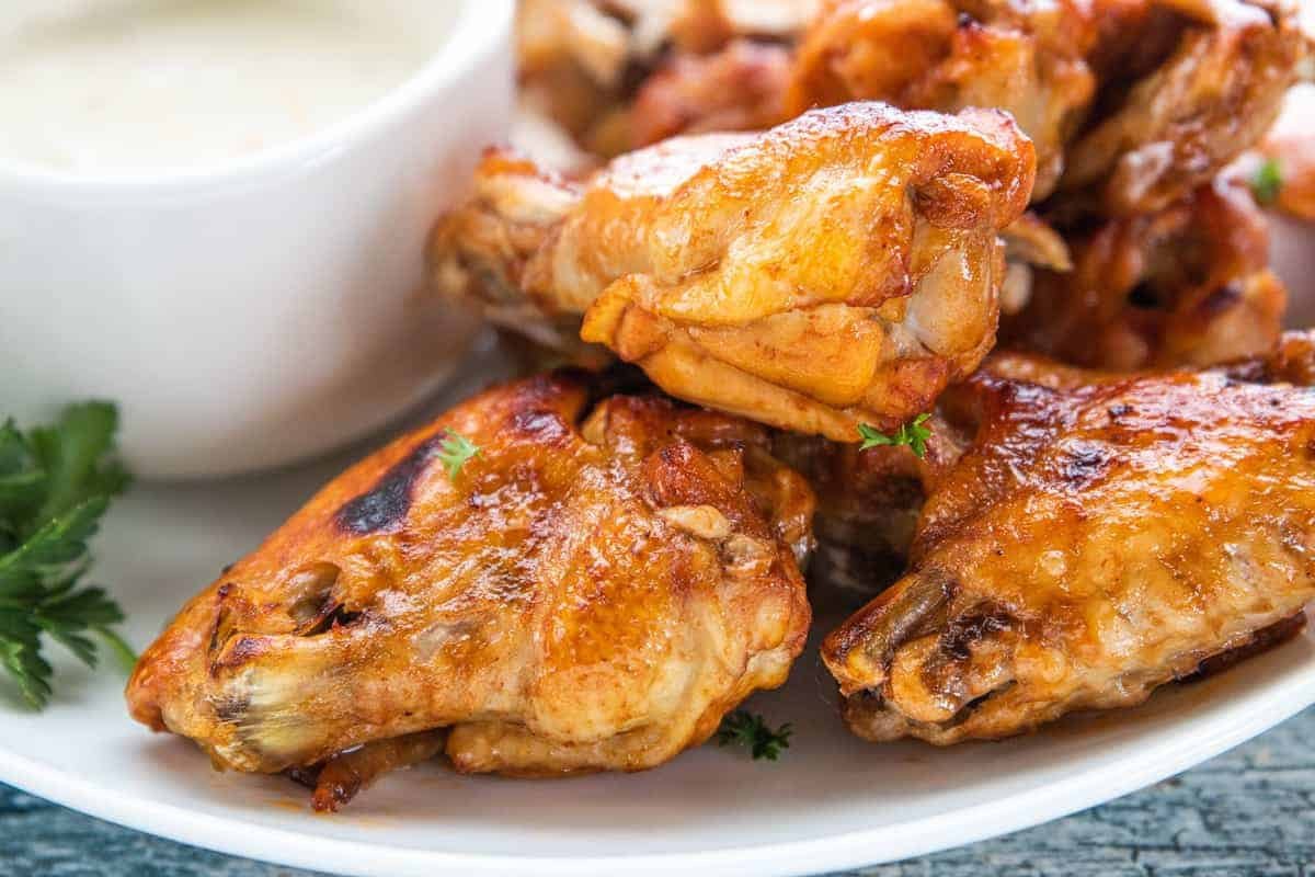 chicken wings on a plate with dipping sauce on the side of the plate.
