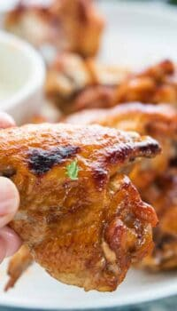 A hand holding a baked chicken wing up close with more wings in the background blurred.
