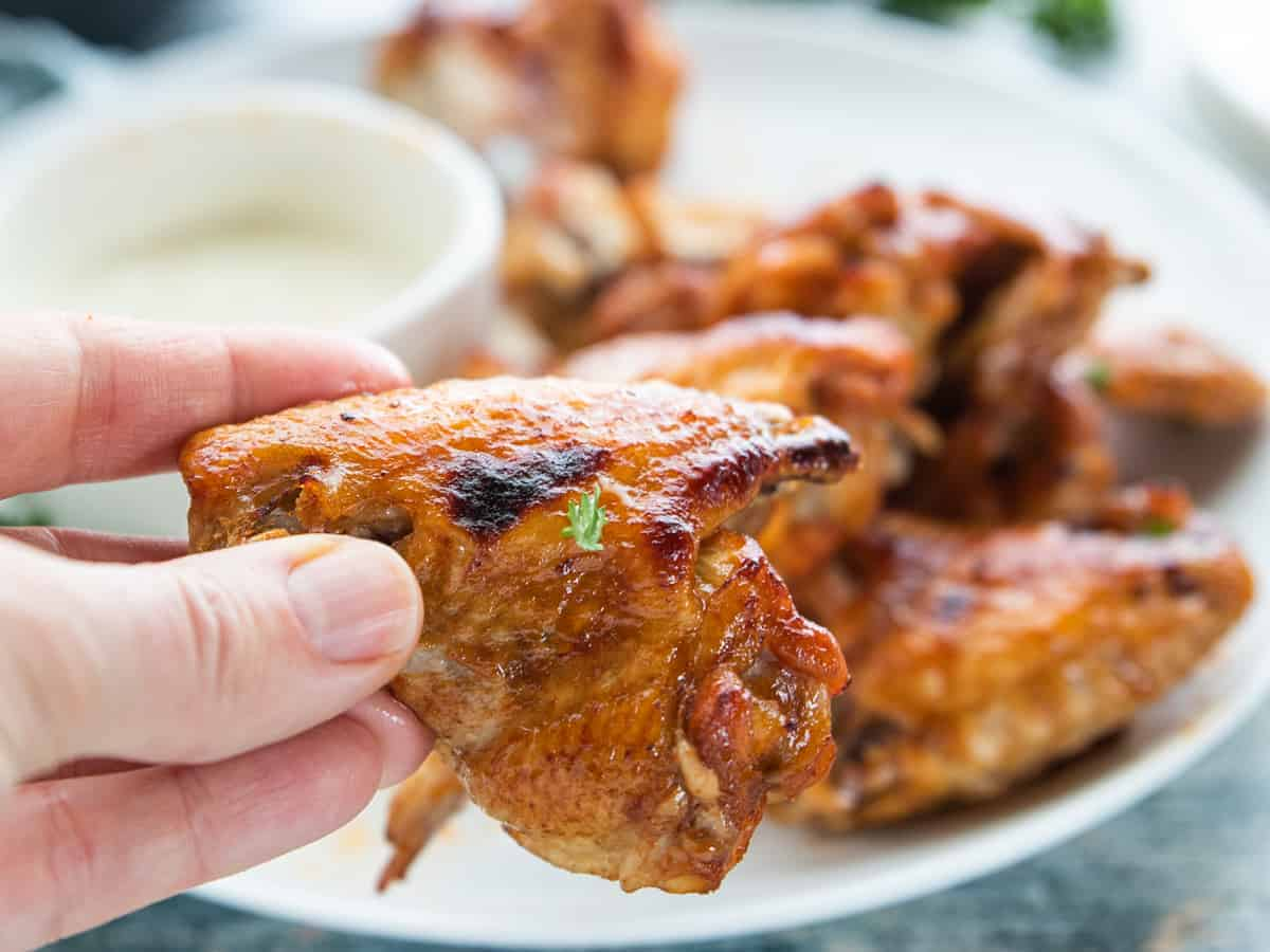 crispy wings on a plate with dipping sauce and a hand holding a chicken wing.