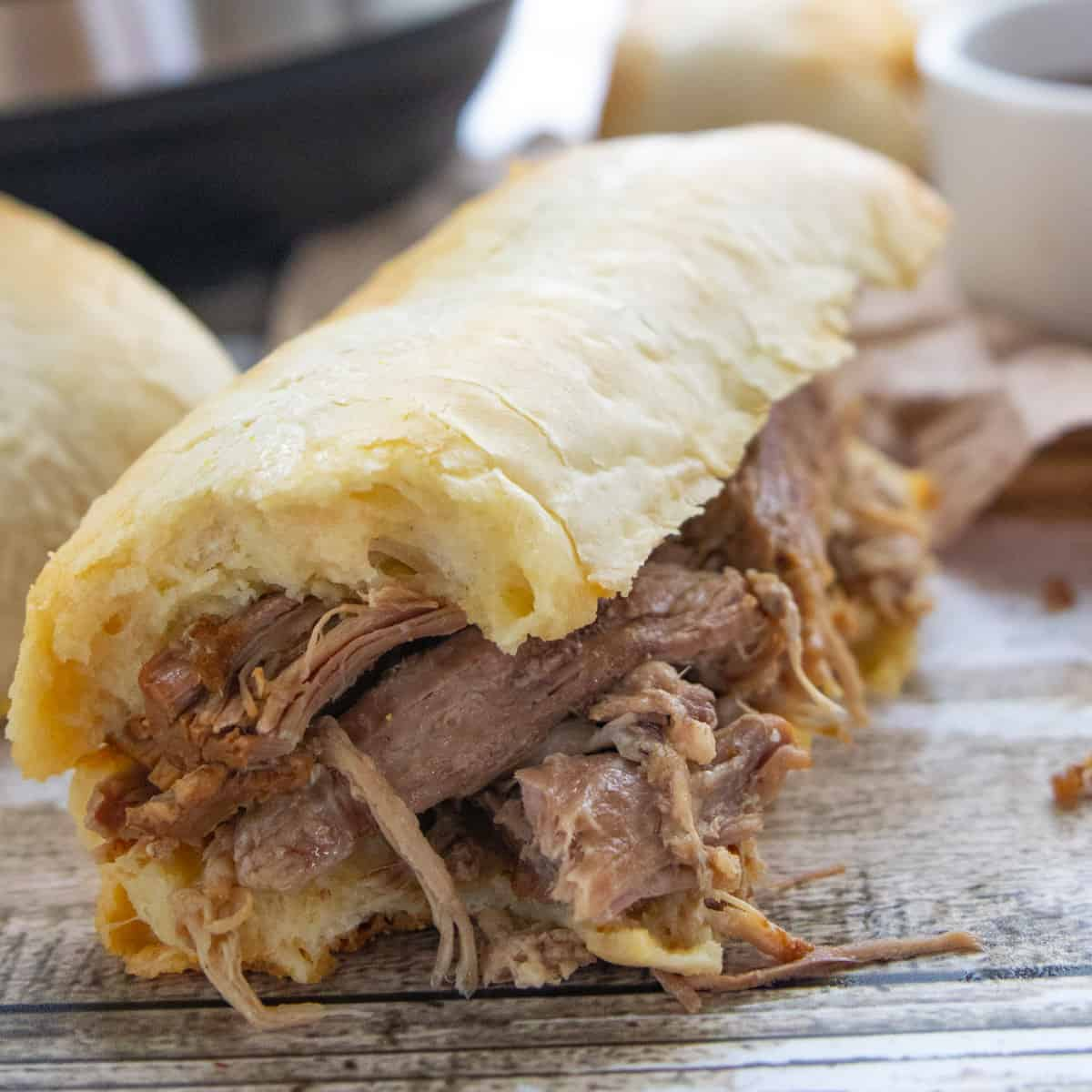 A close up of shredded beef inside a bun with au jus dipping sauce next to it.
