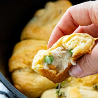 a hand is holding a pot pie stuffed crescent roll with more in the background.