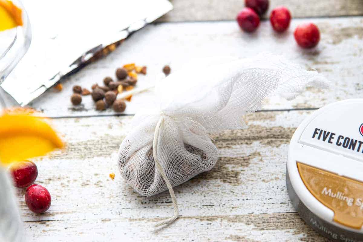 mulling spices being wrapped and tied in a cheesecloth.