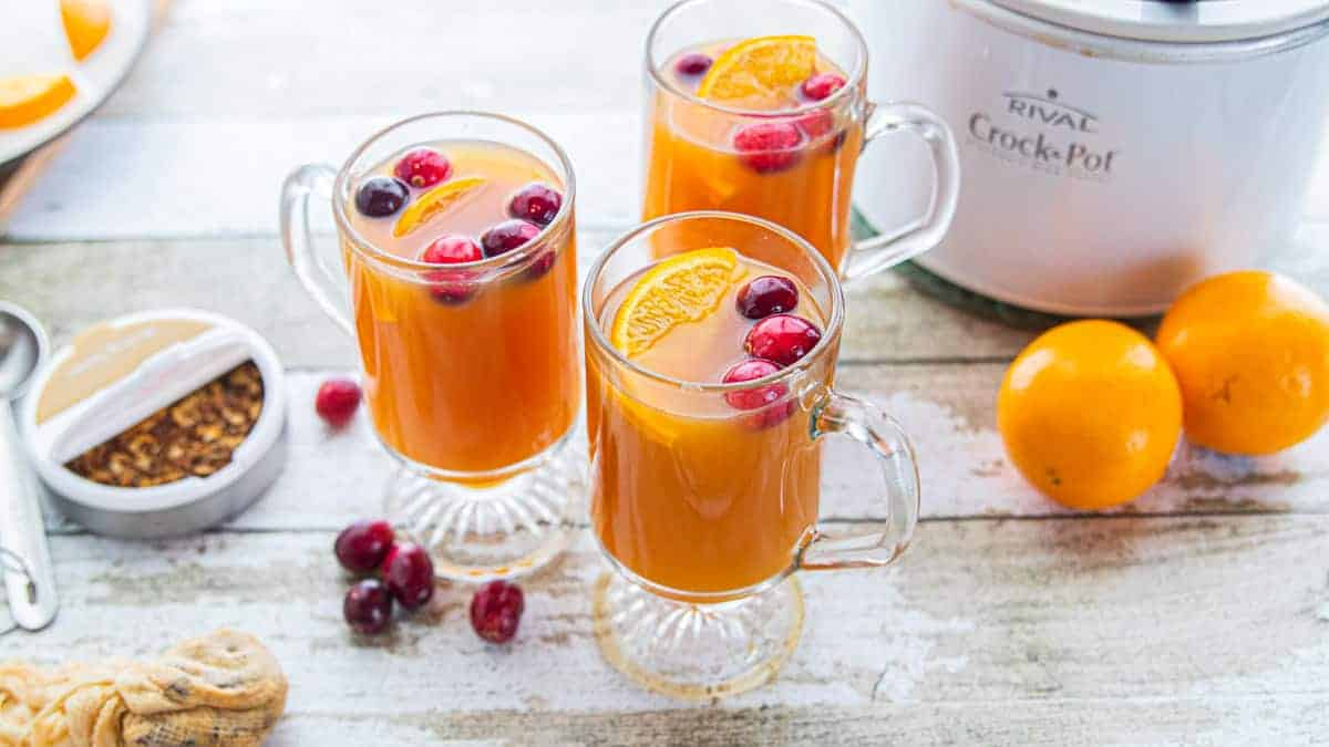 spiced apple cider in glass mugs with whole cranberries and orange slices with mulling spices and a crockpot to the side.