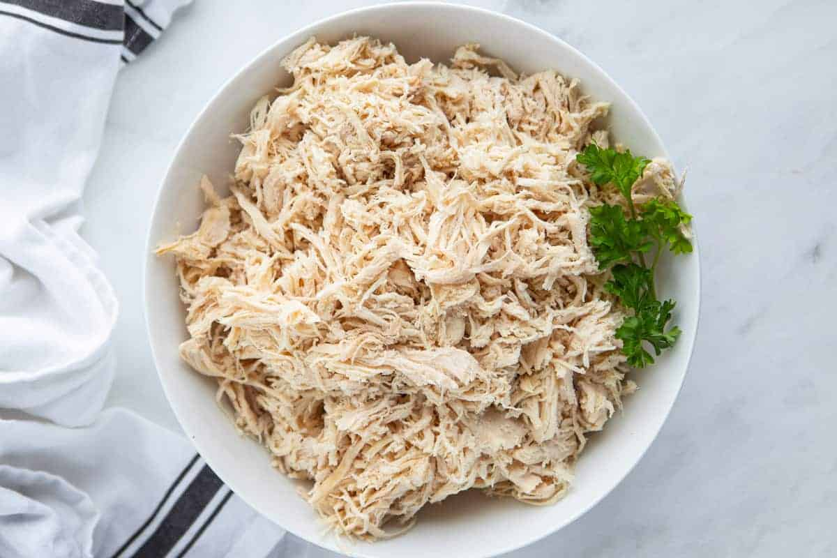 A white bowl filled with shredded chicken breast with a piece of parsley.