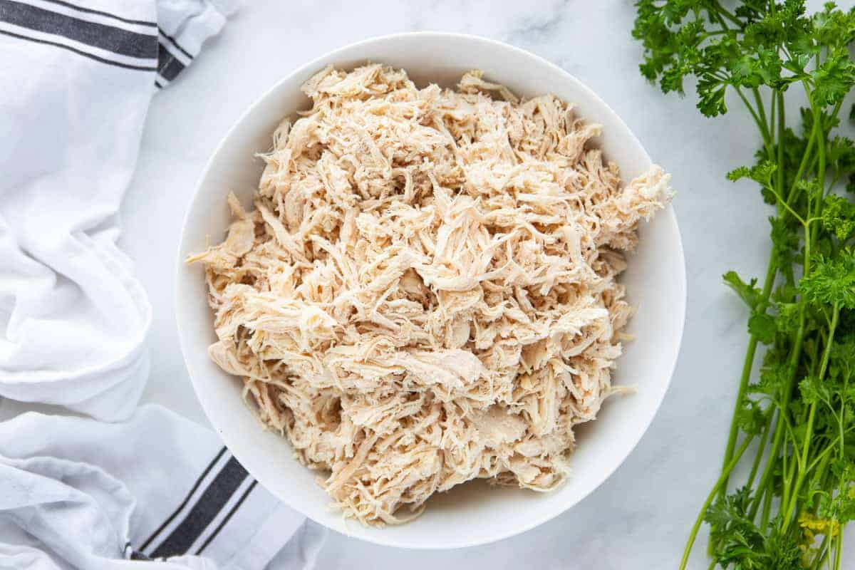 shredded chicken in a white bowl on a white countertop.
