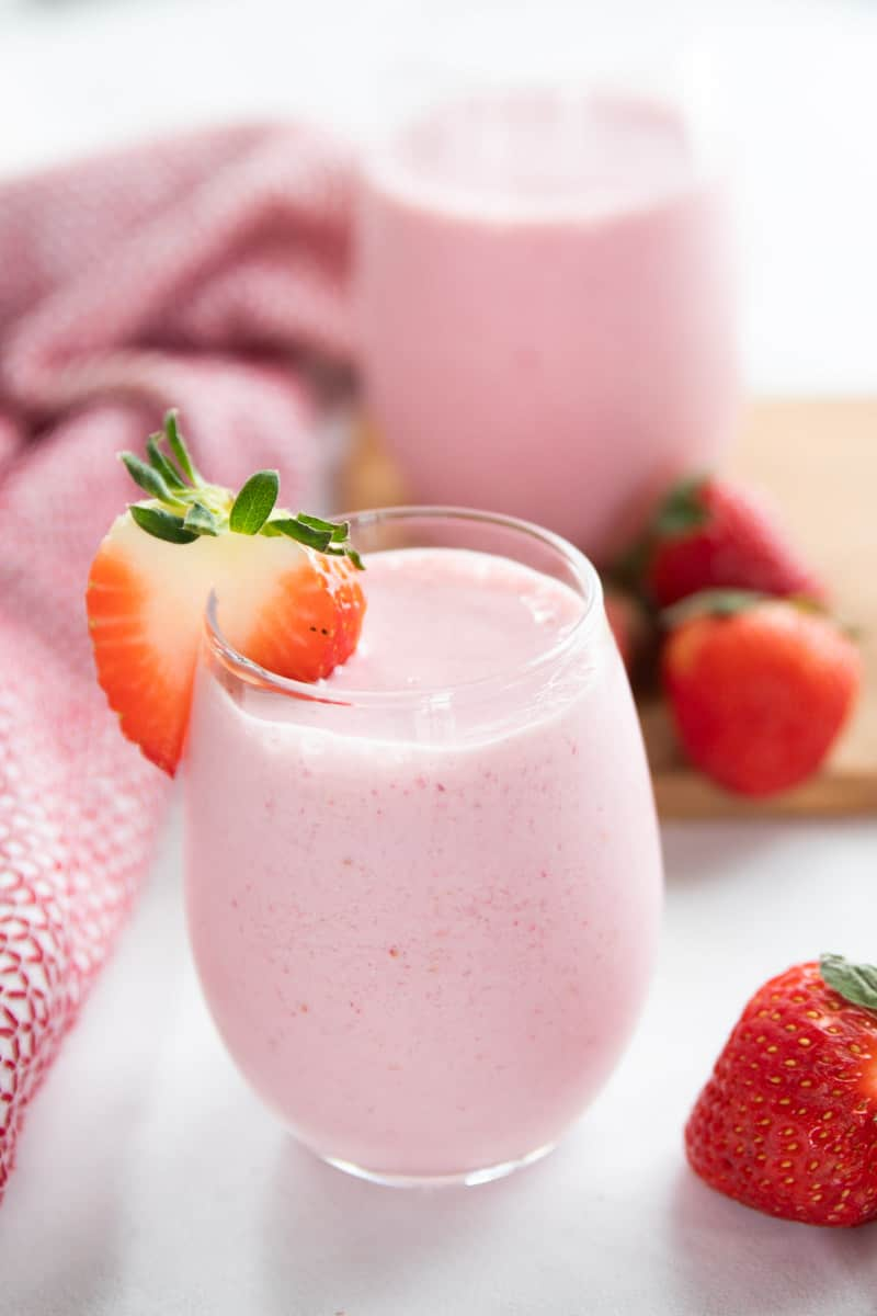 Strawberry Smoothie shown in a clear glass with a half a strawberry on the side of the glass.