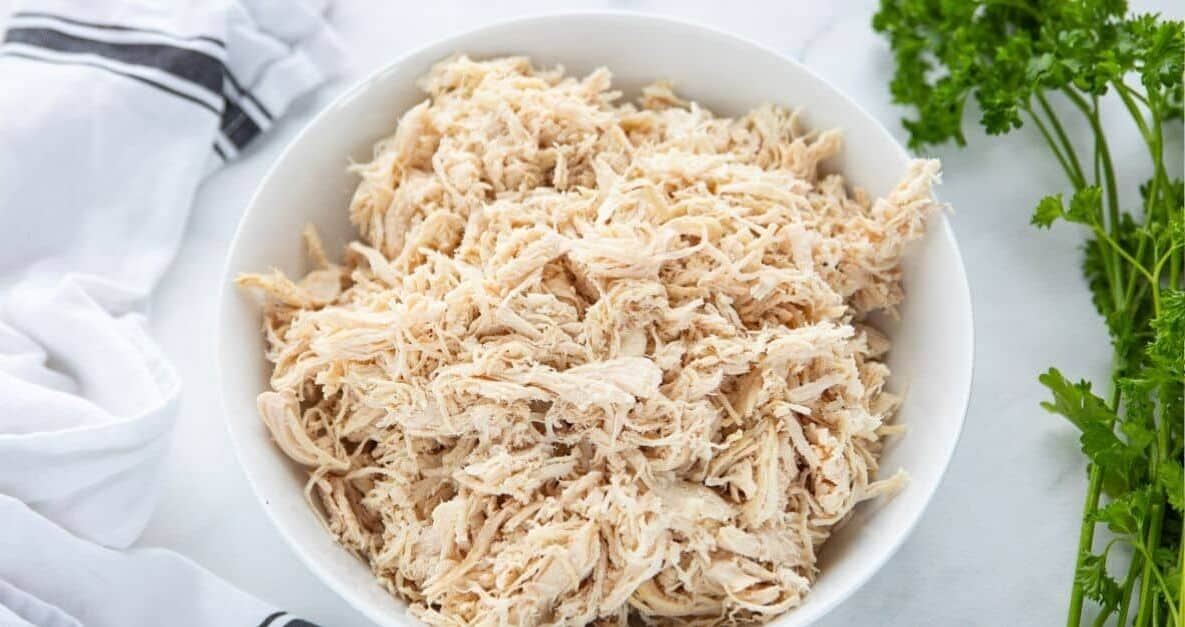 How To Poach Frozen Chicken Breasts in Instant Pot showing shredded chicken in a white bowl with a towel and herbs surrounding the white bowl all on top of a countertop.