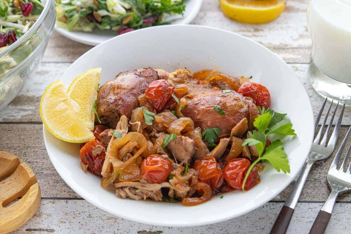 Veggie Packed Kid-Friendly Recipe showing slow cooker chicken and tomatoes in a serving dish on top of a countertop.