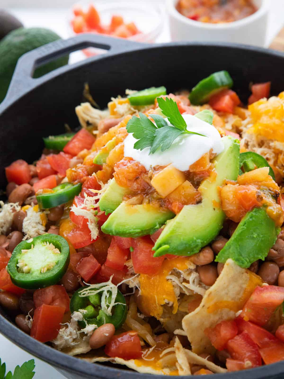 Shredded Chicken Skillet Nachos showing nachos with toppings in a cast iron pan.