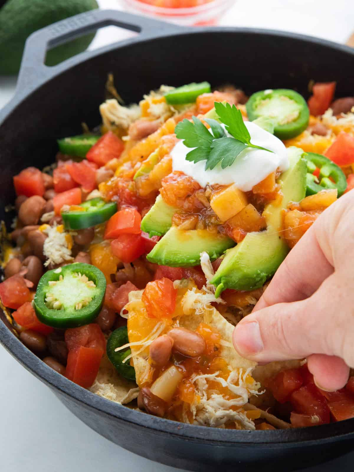 Shredded Chicken Skillet Nachos showing nachos in a cast iron skillet with a hand scooping up a serving.