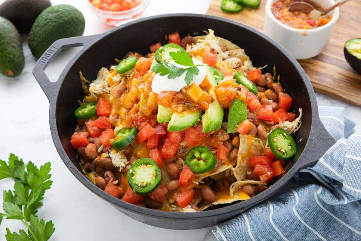 a skillet of chicken nachos topped with vegetables