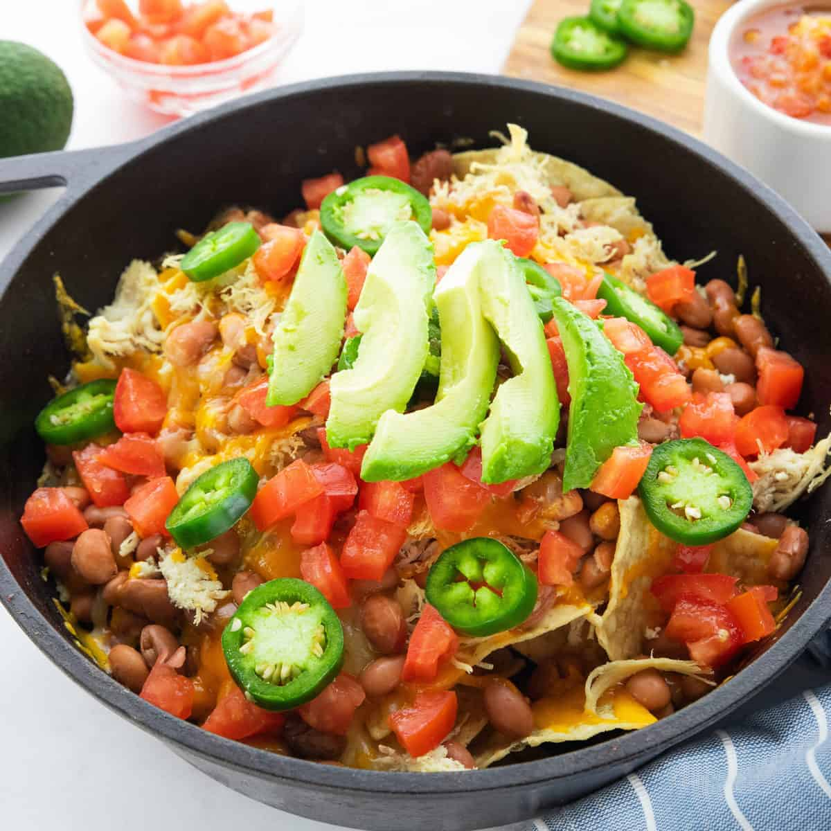 skillet nachos shown in a cast iron skillet with diced tomatoes, jalapeños, beans, and avocados on top.