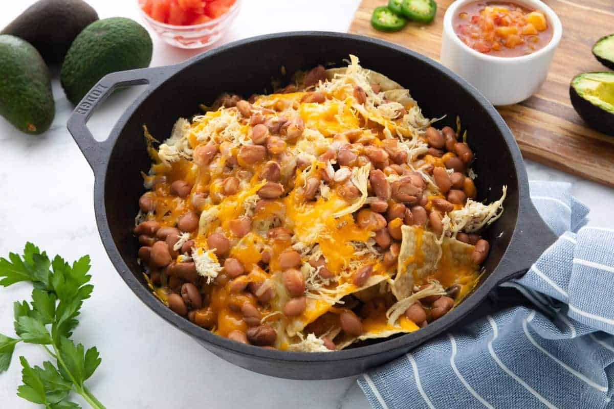 Shredded Chicken Skillet Nachos showing tortilla chips topped with shredded chicken, beans and shredded cheese in a cast iron pan with ingredients surround the pan all on top of a countertop.