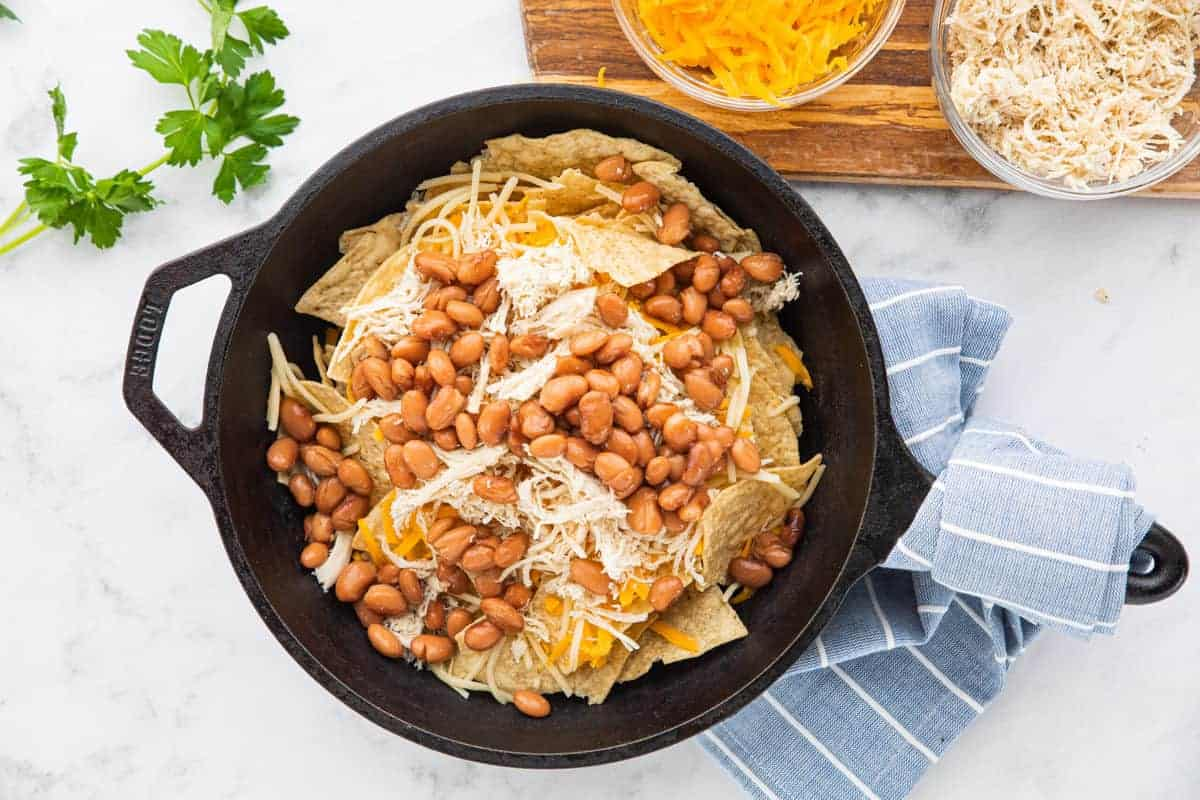 chips, cheese, chicken and beans in a skillet