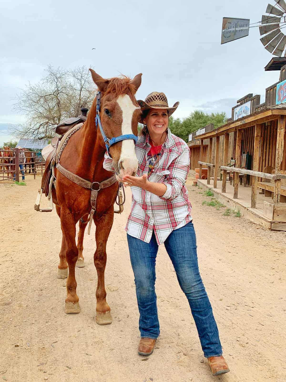 White Stallion Ranch, the Best All-Inclusive Resort in Arizona showing a women standing next to a horse. named Saguaro on the dude ranch.