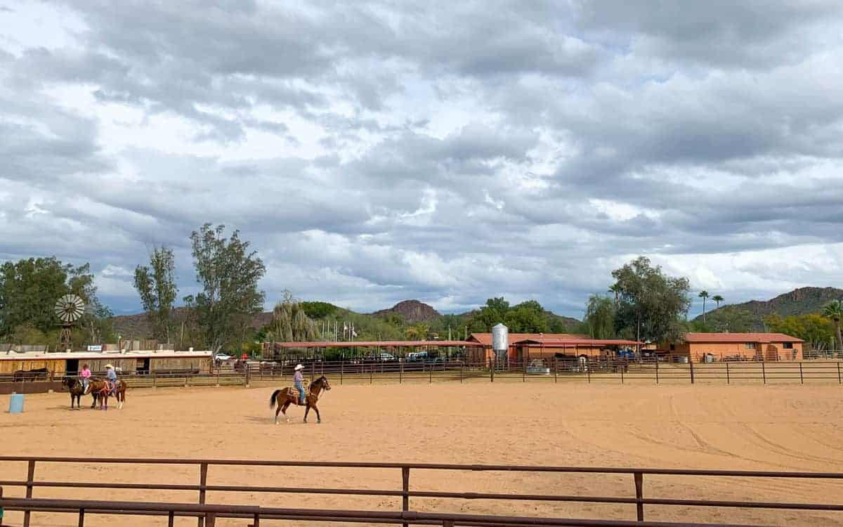 White Stallion Ranch, the Best All-Inclusive Resort in Arizona showing the ranch rodeo where ranchers are riding horses around the arena.