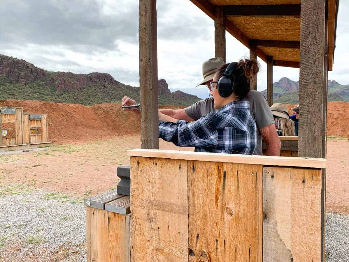 White Stallion Ranch, the Best All-Inclusive Resort in Arizona showing a professional teaching a ranch member in the shooting range.