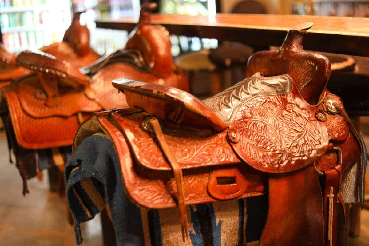 White Stallion Ranch, the Best All-Inclusive Resort in Arizona showing the bar at the dude ranch, which has saddles as the bar seats.