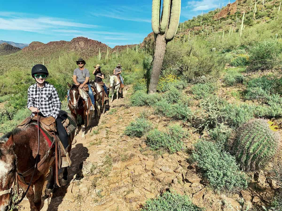 White Stallion Ranch, the Best All-Inclusive Resort in Arizona showing a family of four riding horses through the mountainous region of Arizona.
