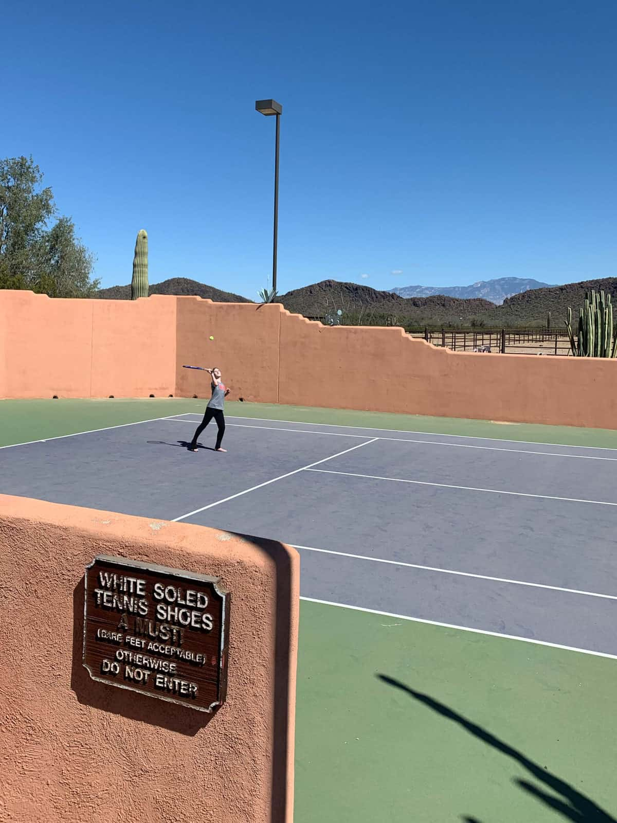 White Stallion Ranch, the Best All-Inclusive Resort in Arizona showing the tennis court at the dude ranch with a young kid playing a game of tennis.