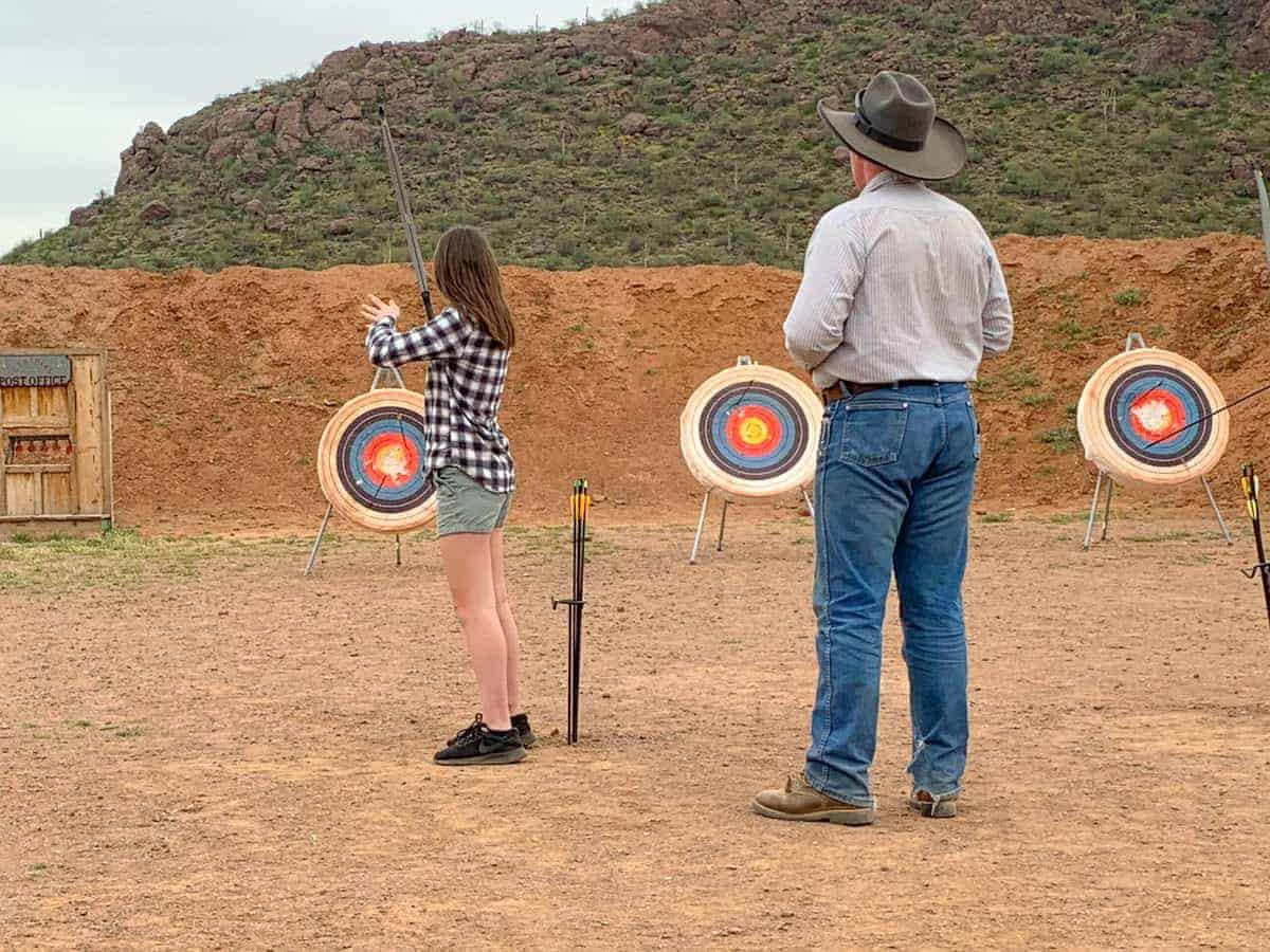 White Stallion Ranch, the Best All-Inclusive Resort in Arizona showing a professional overseeing a young girl practicing archery.