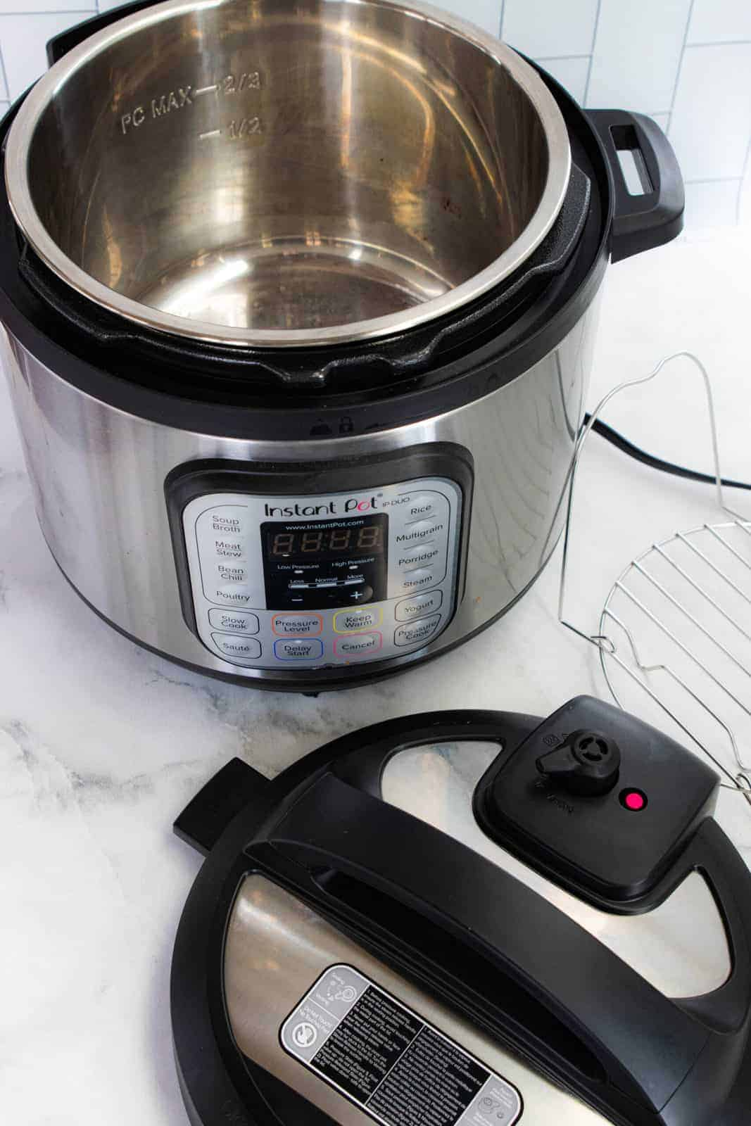 Instant pot showing the unit, wire insert, and lid on a white marble surface.