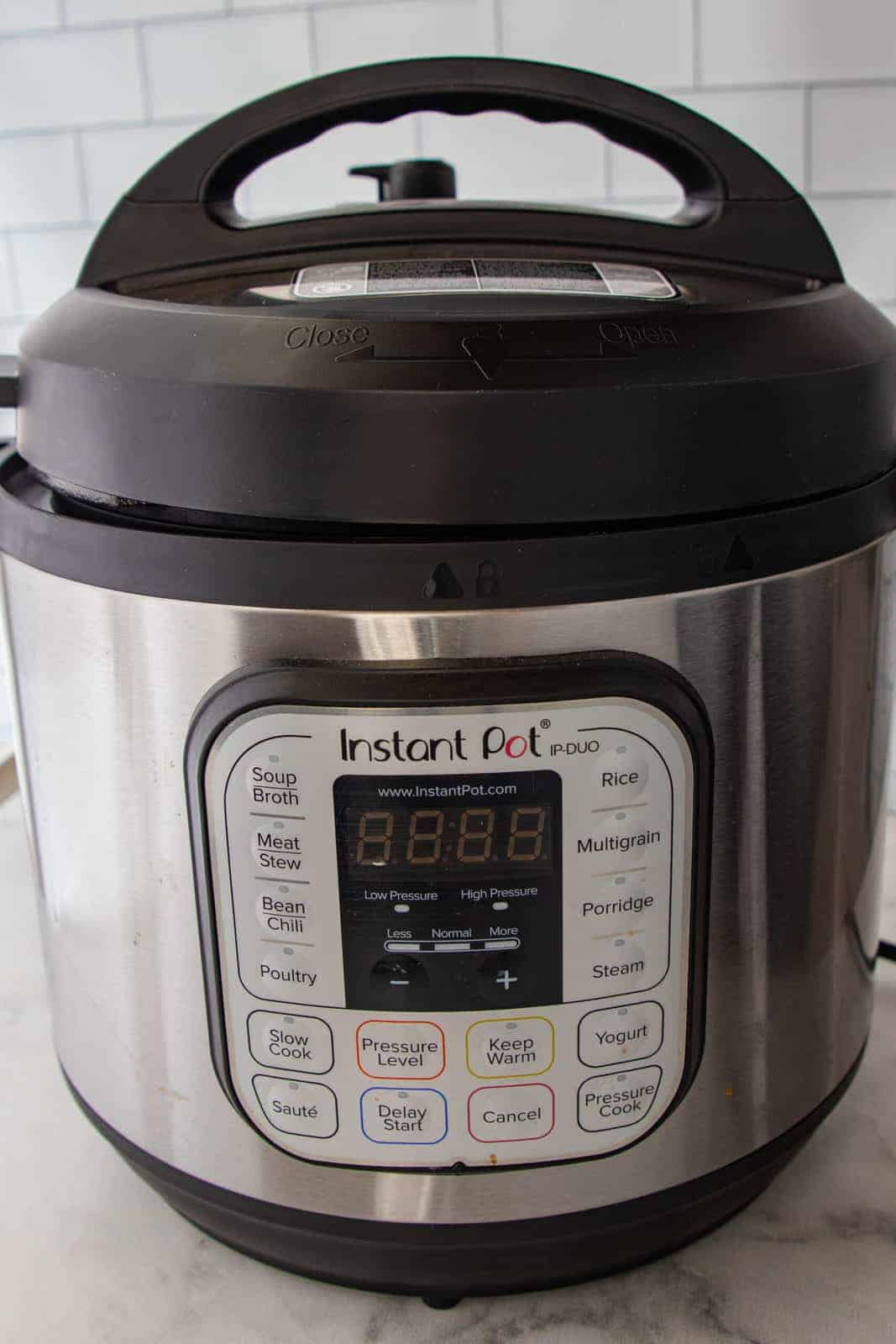 Instant pot showing the unit up close and all the settings it offers including, soup, meat, beans, chili, poultry slow cook, rice, multigrain, porridge, yogurt, and steam.