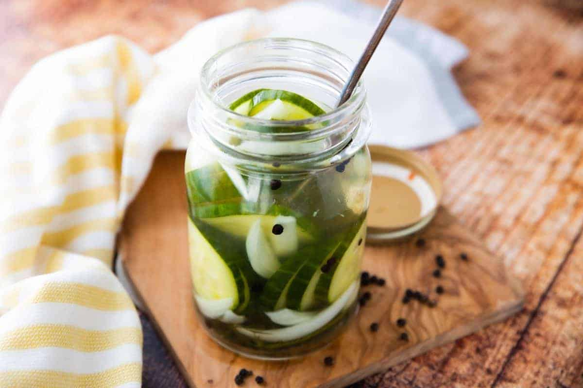 Pickles are shown in a mason jar with onions on a wooden surface with a yellow striped napkin next to it. There is a spoon in the jar.