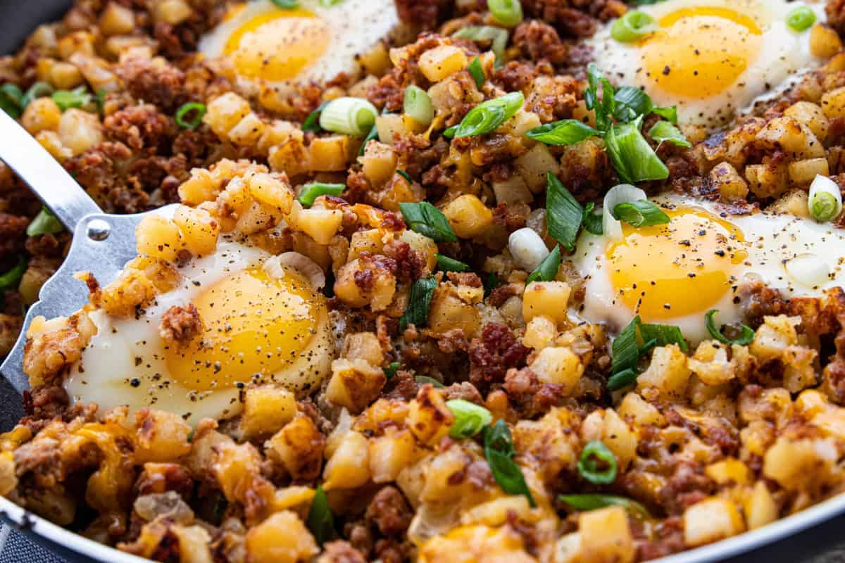 A cowboy breakfast skillet shown up close detailing the diced potatoes, fried eggs, crispy sausage crumbles and green onion slices in a skillet.