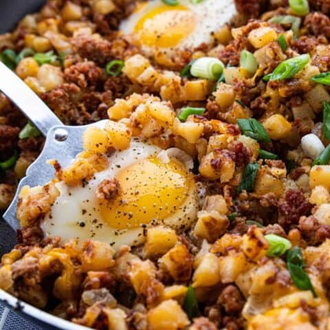 A close up of a cooked skillet scramble showing diced potatoes, bacon bits, cheese, and a fried egg on top.