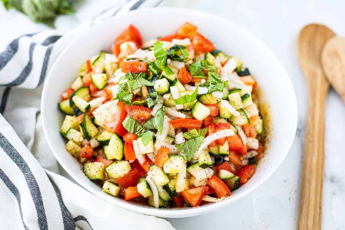 Cucumber tomato salad shown in a white bowl detailing diced tomatoes, cucumber, onion, and basil on a white counter.