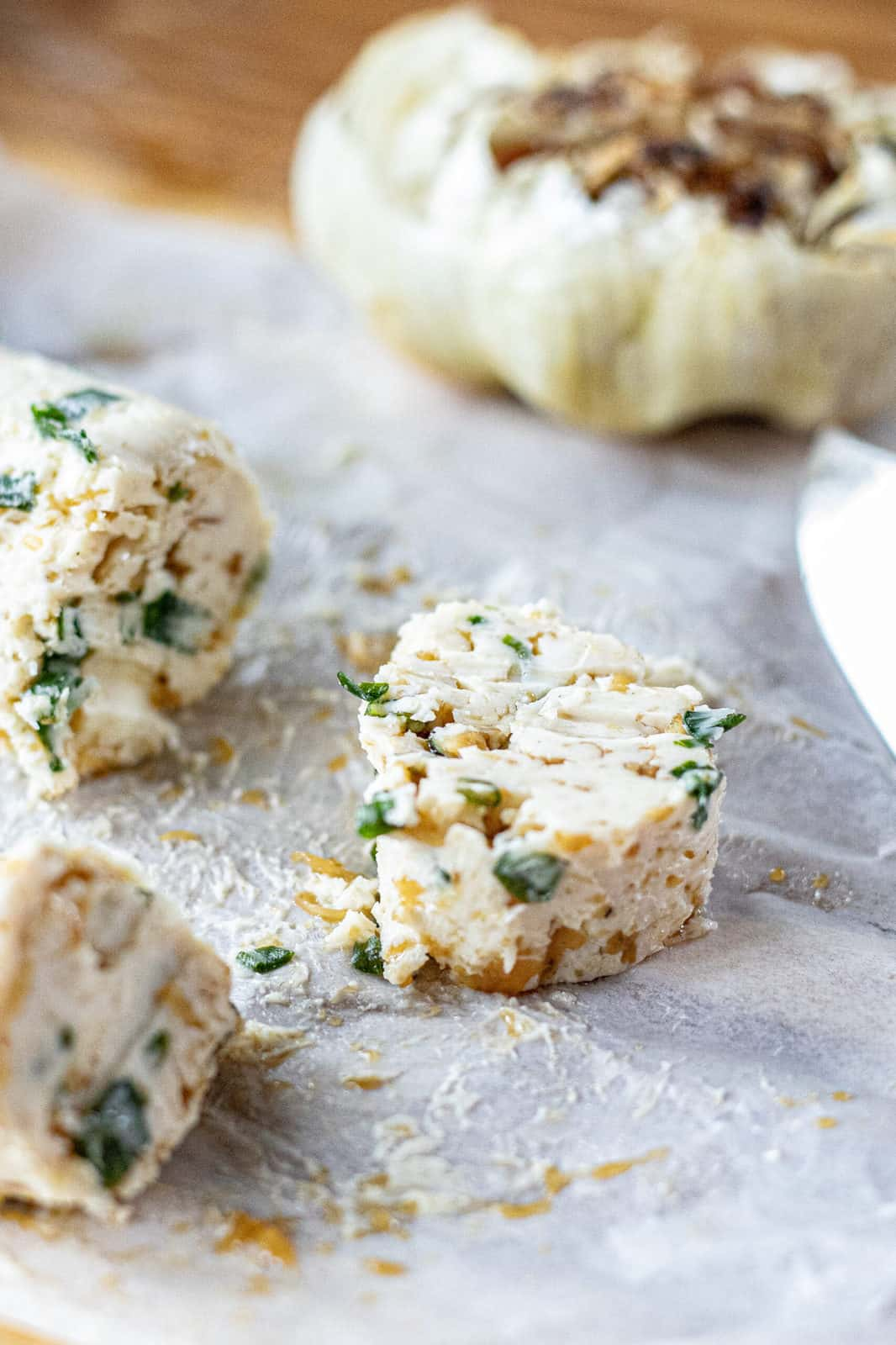 Sliced compound butter with roasted garlic and chives shown up close.